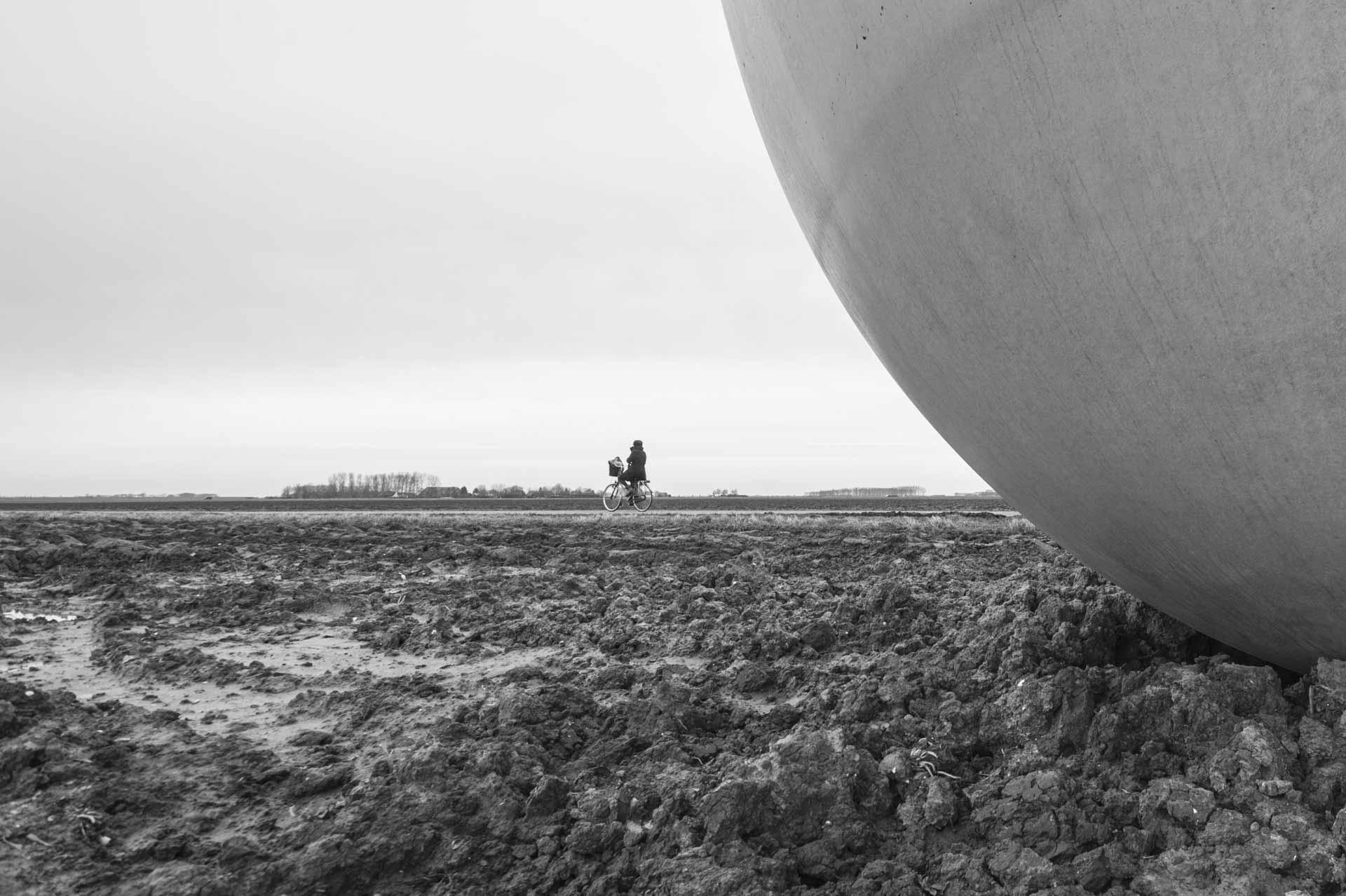 Like suns setting, three meters above true level  LandArt in de Wilhelminapolder 2013  Planning realisatie: 2013 Het weidse landschap van de Koninklijke Maatschap de Wilhelminapolder ten noorden van Goes wordt na de zomer het decor van unieke landschapskunst. In augustus en september wordt het kunstwerk 'Like suns setting three meters above true level' van de Duitse kunstenaar Michael Beutler geplaatst. Het beeldbepalende kunstwerk bestaat uit negen, visueel met elkaar samenhangende betonnen sculpturen, die over ruim duizend hectare landbouwgrond van de maatschap verspreid staan. Het meest westelijke beeld is hemelsbreed ongeveer zeven kilometer verwijderd van het meest oostelijke beeld. De hoogste sculptuur is tien meter en de laagste meet één meter (vanaf maaiveld); deze hoogste en laagste sculptuur staan op het respectievelijk laagste en hoogste punt van het gebied. Staand bij een van de negen grijswitte, bolvormige sculpturen is vanaf die plek één ander beeld waar te nemen. Vanaf de Deltaweg (N256) zijn vier of vijf sculpturen goed te zien. Ook bij het Goese Sas kan het kunstwerk 'beleefd' worden. Het is de bedoeling van de kunstenaar om de toeschouwer bewust te maken van het landschap en van de hoogteverschillen daarin. Photo © Eddy Westveer www.eddywestveer.com All rights reserved  This photo and more are available in high resolution.